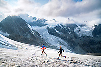 Trail runners descending the glacier beneath the Mettelhorn and Weisshorn, above Zermatt, Switzerland.