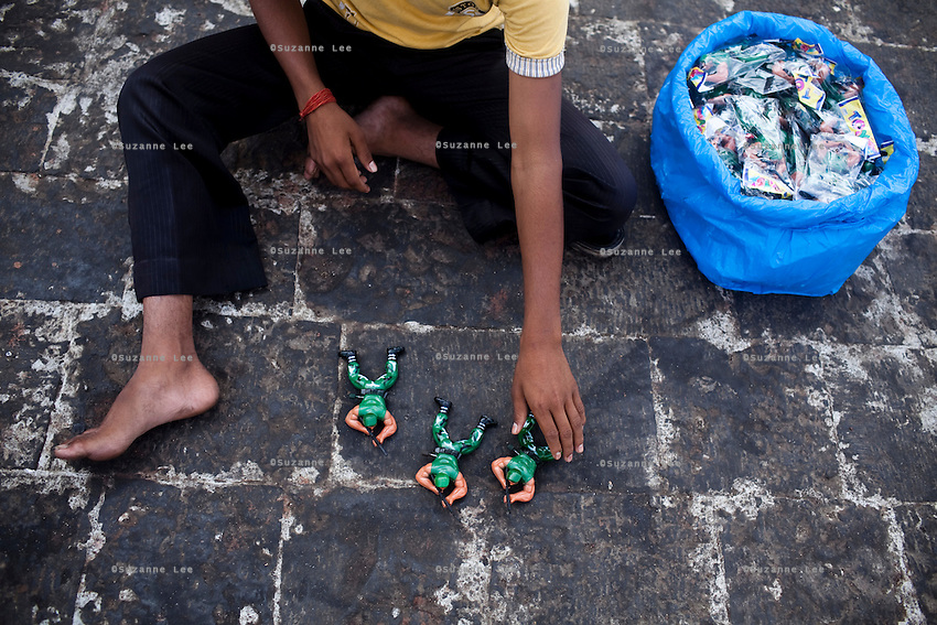 A boy sells commando action figures in front of the Taj hotel, that was attacked in the Mumbai 26/11 in year 2008, on the Marine Drive in Mumbai, India. Photo by Suzanne Lee