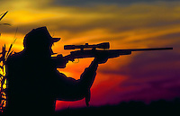 Hunter silhouetted by colorful sky as he takes aim with his rifle.