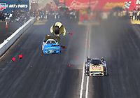 Feb 24, 2019; Chandler, AZ, USA; NHRA funny car driver Jim Campbell crosses the centerline and hits the timing block, disqualifying him, as competitor Tommy Johnson Jr loses a rear tire after an axle failure and explosion during the Arizona Nationals at Wild Horse Pass Motorsports Park. Johnson was uninjured. Mandatory Credit: Mark J. Rebilas-USA TODAY Sports