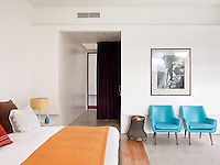 A contemporary, white bedroom with full height windows. A Hermes orange blanket is draped at the foot of the double bed. Two retro blue leather armchairs stand against one wall.