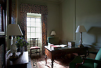 A private study, furnished simply with a desk, upholstered chairs and a set of floral curtains