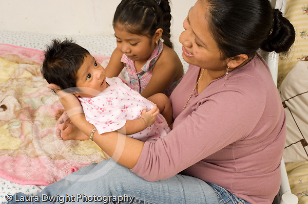 newborn baby girl one month old  Mexican American held by mother with older sister age 4 horizontal