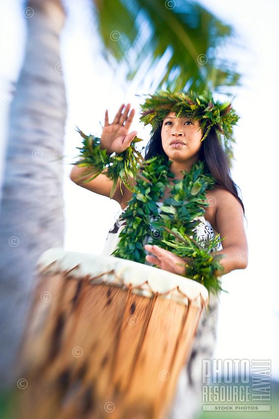 "A Hawaiian woman in kahiko attire plays her pahu (drum) Kanileo, or ""The Voice,"" O'ahu."