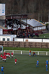 The home team celebrating Marc Berry's goal as Gala Fairydean Rovers (in red) host Gretna 2008 in a Scottish Lowland League match at Netherdale, Galashiels, with the adjoining rugby ground simultaneously hosting a Scottish Cup match between Gala Rugby Club and Heriots Blues. The home club were established in 2013 through a merger of Gala Fairydean, one of Scotland's most successful non-League clubs, and local amateur club Gala Rovers. The visitors were a 'phoenix' club set up in the wake of the collapse of the original club, which had competed for a short time in the 2000s before going bankrupt. The home aside won this encounter 4-1 watched by a crowd of 120 at a stadium which features one of the country's most notable stands, a listed building constructed in 1964 but at the time of this fixture closed to spectators on safety grounds.