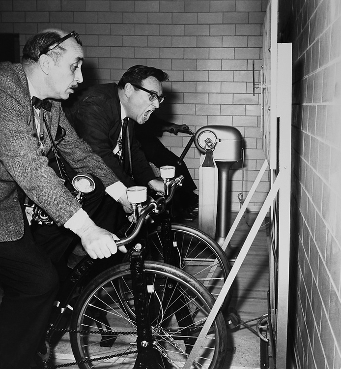 Ed Alley - UPI and Delegate, Bob Schutz, D-Va., Associated Press on bicycle exercycle. (Photo by CQ Roll Call via Getty Images)