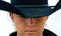 A girl wearing a black hat and jewelry pauses before entering the ring for a horse competition at the Knox County Fair in Mt. Vernon, Ohio.<br />