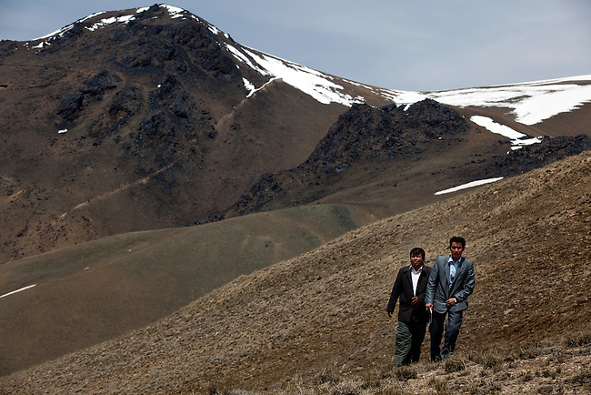08 May 2012, Hajigak Pass, Shibar District, Bamiyan Province, Afghanistan : Minerals Geologist at the Afghan Ministry of Mines Mohammad Amin (right) and head of the GeoScience Department  Mohammad Zahir walking along the ridge at the proposed site of the Hajigak Pass Iron ore mine. The World Bank is funding the proposed development of the Hajigak iron mine through its sponsorship of local Community Development Councils that give local residents a voice in the planning of the mine. The Afghan Ministry of Mines in conjunction with a raft of foreign companies are developing a blueprint for the mine. Plans include construction of infrastructure such as roads to access the remote location, schools and new residential complexes to house mine workers and their families. Local village residents are looking forward to the development that will provide jobs and an increased standard of living in a harsh area that suffers from extreme poverty. Picture by Graham Crouch/World Bank