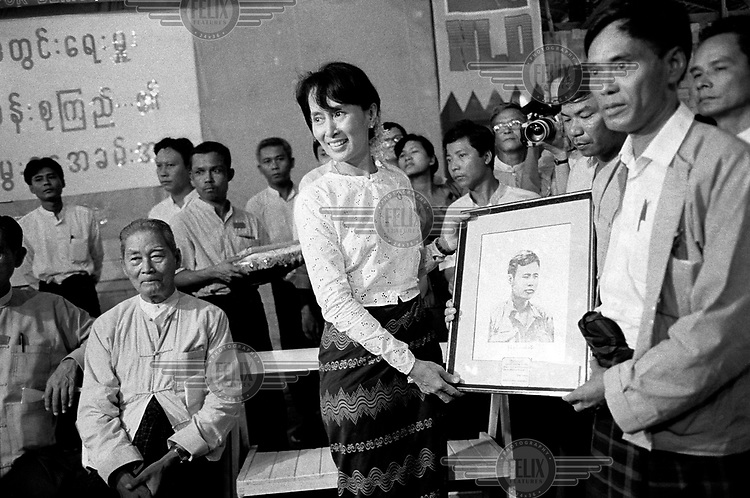 Celebrations marking the 51st birthday of Daw Aung San Suu Kyi, Nobel Peace Prize Laureate and General Secretary of the National League for Democracy (NLD), in the compound of her home. Daw Suu is receiving a portrait of her father General Aung San, Burma's founding father. The late U Kyi Maung, former chairman of the NLD, is seated left.