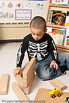 Education preschool 3-4 year olds block area boy playing alone building with wooden blocks vertical
