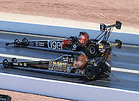 Apr 12, 2015; Las Vegas, NV, USA; NHRA top fuel driver Tony Schumacher (near lane) races alongside Larry Dixon during the Summitracing.com Nationals at The Strip at Las Vegas Motor Speedway. Mandatory Credit: Mark J. Rebilas-