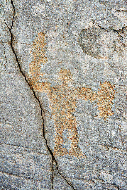 Prehistoric petroglyph rock carvings of a warrior holding a shield and sword by the Camunni people in the iron age between 1000-1600 BC, from Rock 32 of  National Park of Naquane, Lombardy, Italy