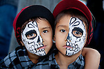 Two boys with matching half-calavera face paint at the Dia de Los Muertos celebration at Hollywood Forever Cemetery in Hollywood, CA