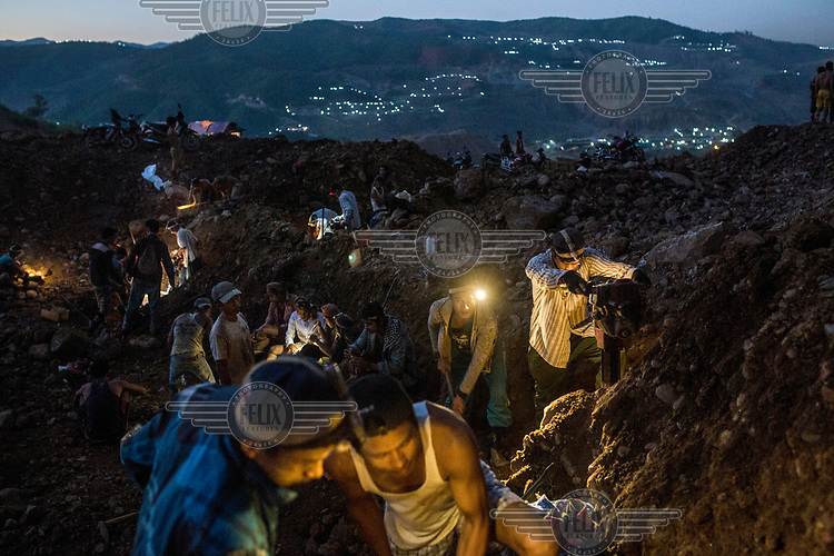 Illegal small-scale miners working by torchlight, going over a pile of company mining waste, looking for jade.