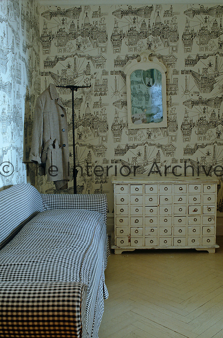 In the living room an antique chest has been arranged against a wall covered in black and white retro wallpaper