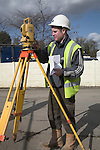 Young male surveyor setting up his theodolite wearing safety clothing and helmet