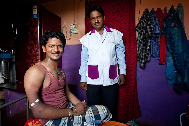 21 May 2013, Divan Sha Nagar, Hubli,  Karnartaka, India:  Irfan M. Sannakki (21) with Pralhad Kulkarni, an Arogya Mitra councellor who has been the conduit to the government  VAS program. Irfan has been receiving treatment for a cancerous tumor in his right arm. The trainee electrician has had 23 sessions of radiation treatment with another 5 still to go. Doctors have told him it will take one and a half years for him to recover fully. The World Bank is financing the Vajpayee Arogyashree Scheme (VAS) that provides advisory and procurement level support to the Karnataka Government.  In turn the Government provides care for those below the poverty line and  covers the cost of their diagnosis and treatment. Irfan has had his costs were 100% covered allowing him to get a new start in life.  Picture by Graham Crouch/World Bank