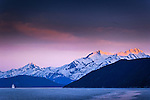 """Holland America Cruise Ship """"Amsterdam"""" sailing through Lynn Canal, Inside Passage, near Haines, SE Alaska at sunset in early summer.  Chilkat Mountains in the background."""