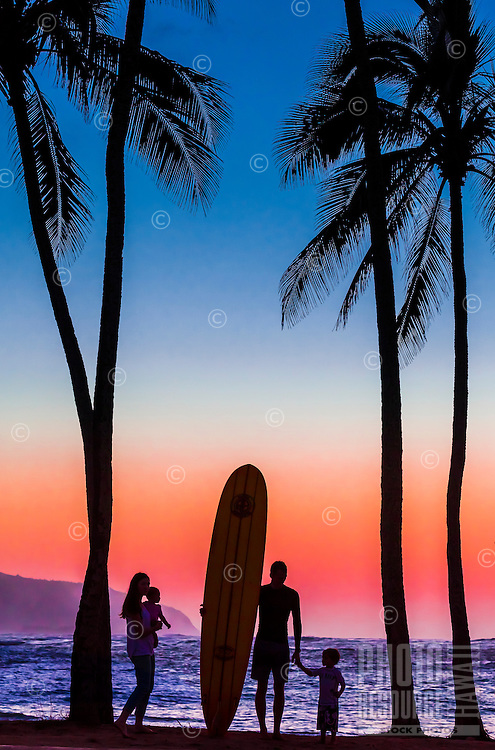 A surfer and his family enjoy the view of Ka'ena Point at sunset from Hale'iwa Beach Park, O'ahu.