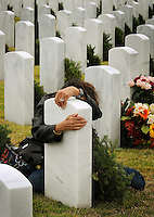 Kelly.Jordan@jacksonville.com--121413--Vivian Jantzen, of Orange Park, hugs the headstone at her husband Ross Jantzen's grave as over hundreds and hundreds of people came out to lay wreaths on graves as the Jacksonville National Cemetery hosted Wreaths Across America, a remembrance wreath-laying ceremony to honor and remember our nation's Veterans at the Jacksonville National Cemetery Saturday December 14, 2013. Jantzen, who served in the Navy for 24 years passed away June 2012. The Patriot Guard Riders in Florida, Veterans Service Organizations, private citizens and a host of other organizations and businesses coordinated the event to honor Veterans of each branch of the military, the Merchant Marines as well as Prisoners of War and those still Missing in Action.(The Florida Times-Union, Kelly Jordan)