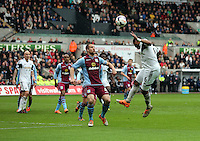 Sunday, 26 April 2014<br /> Pictured: Ashley Williams of Swansea (R) attempts to cross the ball with a header overRon Vlaar of Aston Villa (C)<br /> Re: Barclay's Premier League, Swansea City FC v Aston Villa at the Liberty Stadium, south Wales.