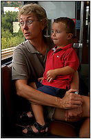 A toddler rides on the lap of his grandmother while taking a train into Pittsburgh. Model released.