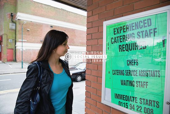 Young Czech woman reading a notice advertising for catering staff vacancies,