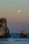 Full moon sets at dawn over the base of Morro Rock and the Pacific Ocean, Morro Bay, California