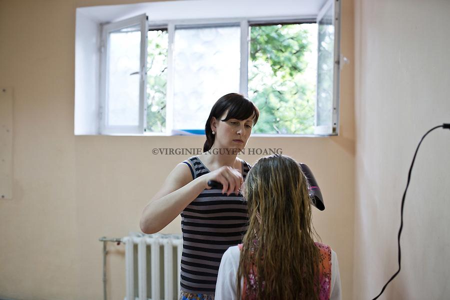 UKRAINE, Mariupol: Nadia has to give birth in Mariupol, when they escaped from Donetsk, she was 5months pregnant. Here, she's drying Julia's hair in the ping-pong room. <br /> <br /> UKRAINE, Mariupol: Nadia a du donner naissance &agrave; Mariupol, quand ils sont parti de Donetsk, elle &eacute;tait enceinte de 5 mois. Ici, elle s&egrave;che les cheveux de Julia dans la salle de ping-pong.