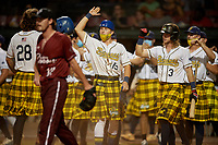 Savannah Bananas Nick Clarno (15), Kyler Marquis (3), and Josiah Siegel (11) congratulate Daniel Oberst (28) after scoring a run during a Coastal Plain League game against the Macon Bacon on July 15, 2020 at Grayson Stadium in Savannah, Georgia.  Savannah wore kilts for their St. Patrick's Day in July promotion.  (Mike Janes/Four Seam Images)