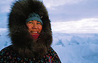 Portrait of a Native Alaskan woman wearing a fur hat and traditional coat in the bitter Alaskan cold. Alaska.
