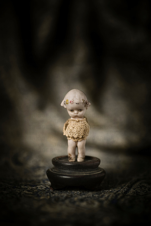 Vintage miniature porcelain doll with sad expression in spotlight