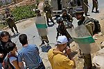 Israeli, International & Palestinian protesters attempt to pass a road block moments before the detonation of an Israeli concussion grenade during a demonstration against Israel's controversial separation barrier in the West Bank town of Beit Jala near Bethlehem on 04/07/2010.