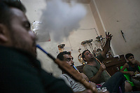 June 09, 2015 - Beirut, Lebanon: Palestinian refugees smoke narguile as they gather inside a coffee shop also used as an office for those that move as refugees/migrants into Europe in Shatila refugee camp. (Photo/Narciso Contreras)