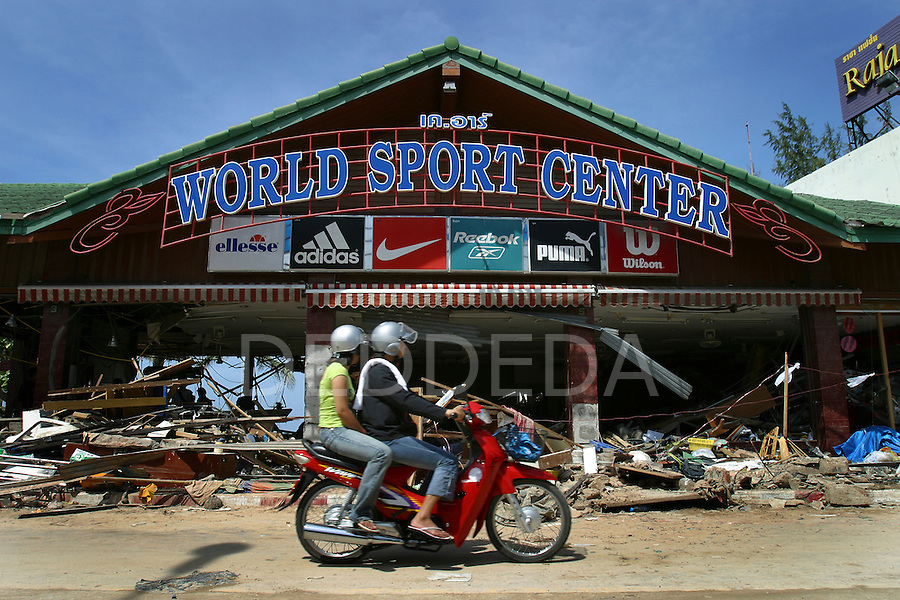 A couple survey the damage of a gutted sporting goods store from their scooter after the tsunami destroyed Patong Beach on Phuket Island, Thailand. On December 26, 2004, a major earthquake generated tsunamis that ravaged coastlines from Southeast Asia to Africa. Approximately 275,000 people were killed and tens of thousands were left homeless, making it one of the deadliest natural disasters in modern history.