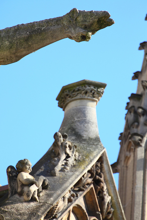 A particular of the top of the church of Saint Séverin in Paris, with a small marble angel and a gargoyle against the blue sky. Digitally Improved Photo.