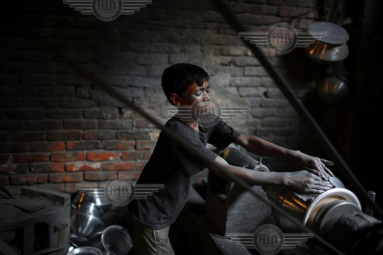 Children working in a silver cooking pot factory in Old Dhaka. The children work 10 hour days in hazardous conditions, for a weekly wage of 200 taka (3 USD)...