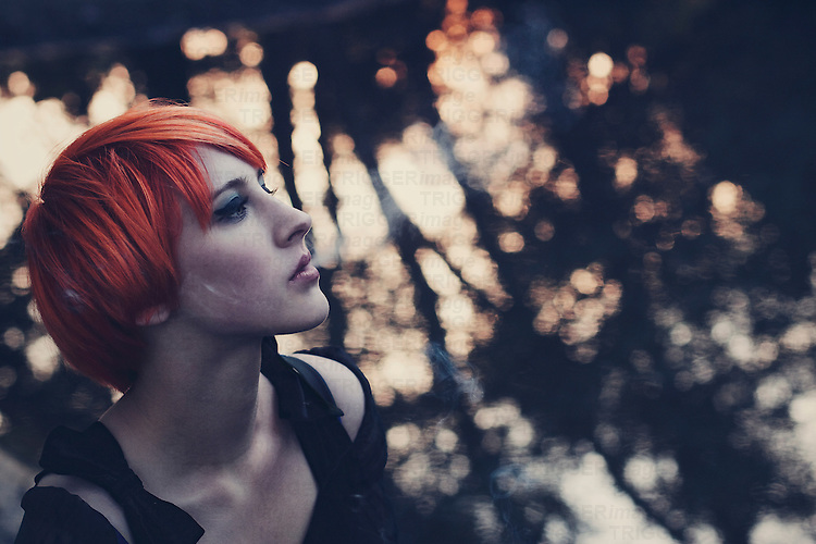 Profile portrait of a young girl with short orange hair and dark make up, looking away, blowing smoke, with blurry lake background.