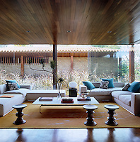 Three Eames walnut stools sit on the edge of a rug by Mira Lehr in the living room