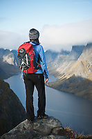 Female hiker takes in view of dramatic mountain landscape from Reinebringen, Lofoten Islands, Norway