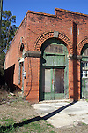 An old brick garage or filling station sits boarded up dreaming of the past.