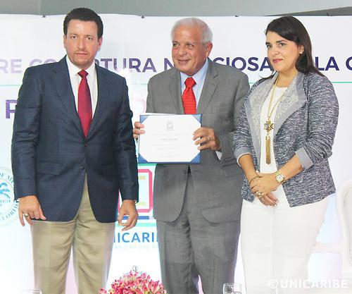 """El momento de la entrega a Regalado del certificado como """"Profesor Honorífico"""" de UNICARIBE por parte del Rector Aybar Martín y su esposa Shahily Pimentel de Aybar."""