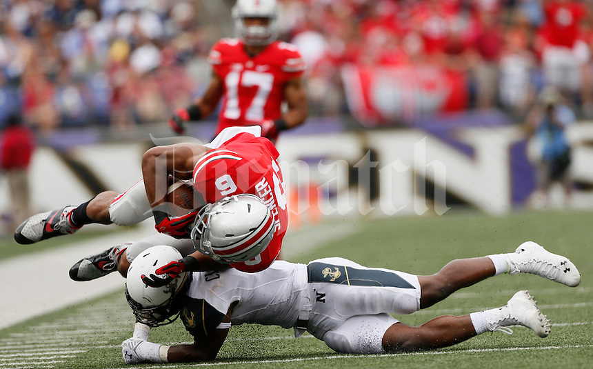 Ohio State Buckeyes wide receiver Evan Spencer (6) is upended by Navy Midshipmen cornerback Brendon Clements (1) during Saturday's NCAA Division I football game at M&T Bank Stadium in Baltimore on August 30, 2014. Ohio State won the game with a final score of 34-17. (Dispatch Photo by Barbara J. Perenic)