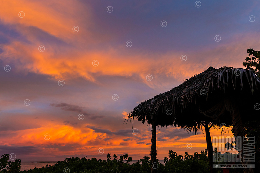 An open beach chair under a thatched roof overlooking Waialua Beach at sunset, North Shore, O'ahu.