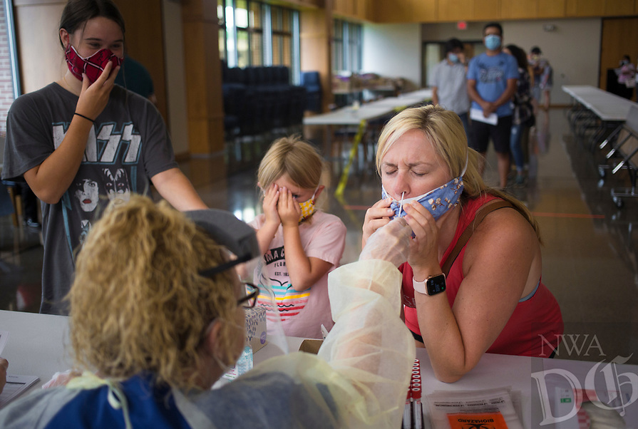 """Jessica Daniels of Cave Springs (right) takes a covid-19 test as her daughters Channing Daniels, 15, (from left) and Annie Daniels, 5, watch, Sunday, June 28, 2020 at St. Raphael Catholic Church in Springdale. The Arkansas Department of Health partnered with the church to host a covid-19 screening for the parishioners of the church. Their goal was to administer 250 tests. """"They have a large Hispanic congregation greater than 70 percent so we're trying to offer it to their members,"""" said Cassie Cochran, Northwest Region Director. """"They're comfortable coming here, and it's convenient because they have eight masses on Sunday."""" The Arkansas Department of Health will hold another screening on Tuesday, June 30th at the Washington County Health Unit in Fayetteville that will be open to the general public from 4pm to 8pm. Check out nwaonline.com/200629Daily/ for today's photo gallery. <br /> (NWA Democrat-Gazette/Charlie Kaijo)"""