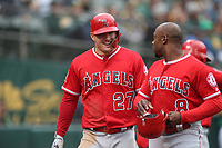 OAKLAND, CA - JUNE 15:  Mike Trout #27 of the Los Angeles Angels of Anaheim celebrates with teammate Justin Upton #8 after scoring a run against the Oakland Athletics during the game at the Oakland Coliseum on Friday, June 15, 2018 in Oakland, California. (Photo by Brad Mangin)
