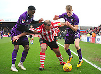 Lincoln City's Matt Rhead shields the ball from Grimsby Town's Mitch Rose, left, and Luke Hendrie<br /> <br /> Photographer Andrew Vaughan/CameraSport<br /> <br /> The EFL Sky Bet League Two - Lincoln City v Grimsby Town - Saturday 19 January 2019 - Sincil Bank - Lincoln<br /> <br /> World Copyright © 2019 CameraSport. All rights reserved. 43 Linden Ave. Countesthorpe. Leicester. England. LE8 5PG - Tel: +44 (0) 116 277 4147 - admin@camerasport.com - www.camerasport.com