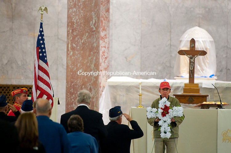 WATERBURY, CT--- -12075JS02--Pat Musco, right, holds a cross of flowers while God Bless America is played following a Mass Monday at the Basilica of the Immaculate Conception in Waterbury. <br /> Jim Shannon Republican-American