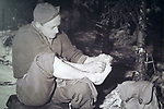 Foto: VidiPhoto<br /> <br /> BASTOGNE – Op 16 december is het precies 75 jaar geleden dat Hitler een laatste serieuze poging deed om de geallieerde opmars tot stilstand te brengen en de haven van Antwerpen in handen te krijgen. Het Ardennenoffensief was tegen de zin van de Duitse generaals, omdat er onvoldoende getrainde manschappen beschikbaar waren en nauwelijks brandstofvoorraden. In totaal kwamen er 160.000 militairen aan zowel Duitse als geallieerde zijde om het leven. Foto: Een Amerikaanse militair in de bossen bij Bastogne die bevriezing van zijn voeten probeert te voorkomen.