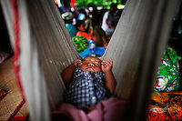 A HIV-positive Ei Ei Phyu, who lives at the hospice with his also HIV-positive mother sleeps in a hammock at the at the HIV/AIDS hospice, founded by a member of the National League for Democracy (NLD) party in suburbs of Yangon May 26, 2012.   REUTERS/Damir Sagolj (MYANMAR)